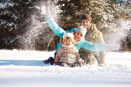 ropa de invierno: Familia atractivo que se divierten en un parque de invierno