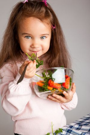 Preschool girl holding bowl with vegetable salad photo