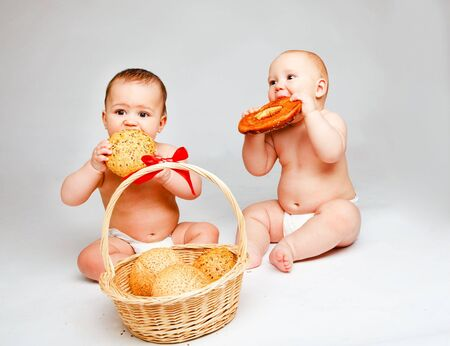 Two sweet babies in diapers eating buns photo