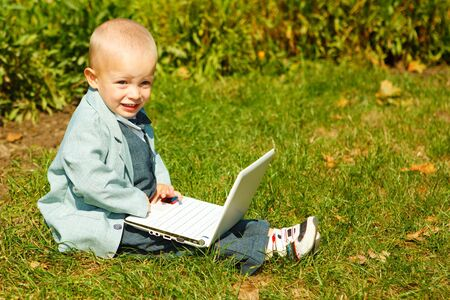 A cute blond kid  sitting on grass with laptop photo