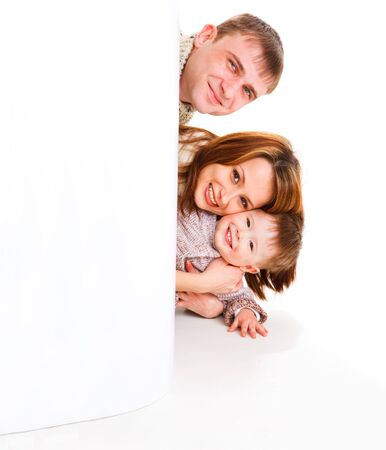 Gorgeous young family, hiding behind a large blank poster photo