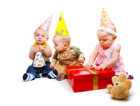 surprised child: Three lovely toddlers in party hats Stock Photo