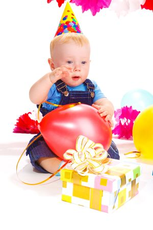 red balloon: Baby in a party hat happy to receive a present Stock Photo