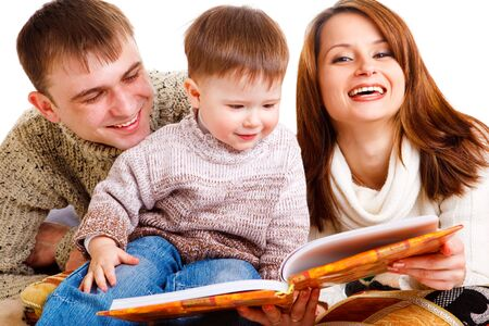 Parents reading a book to their lovely kid photo