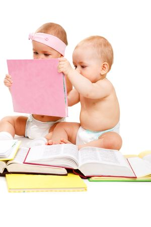 interested baby: Two lovely kids holding a book and reading it, over white