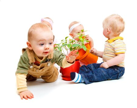 A group of beautiful babies sitting, one is crawling photo