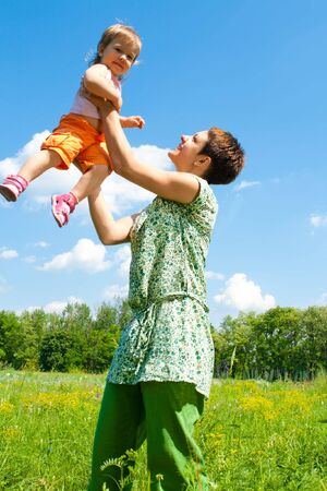 Mother playing with her lovely daughter on the meadow Stock Photo - 6536849
