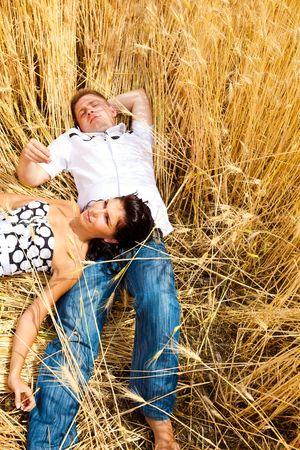 A sweet couple lying in wheat field Stock Photo - 6553659