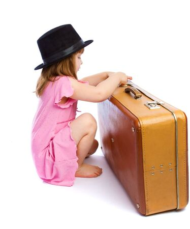 Preschool girl unlocking an old suitcase, isolated Stock Photo - 6732116