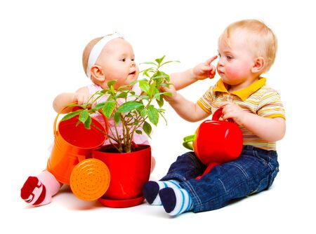 Two cute baby friends sit with watering pots Stock Photo - 6732125