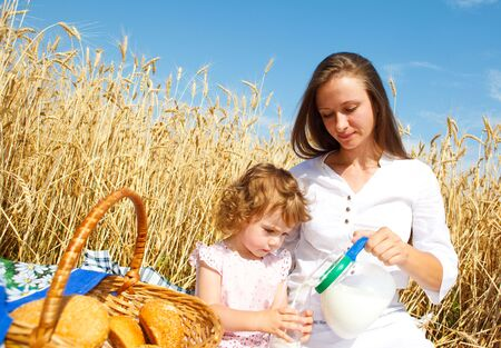 Mother and daughter having breakfast in field photo