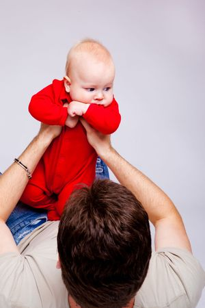fathering: Father playing with his infant son, over gray