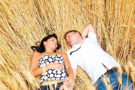 Adorable couple lying in the wheat field photo