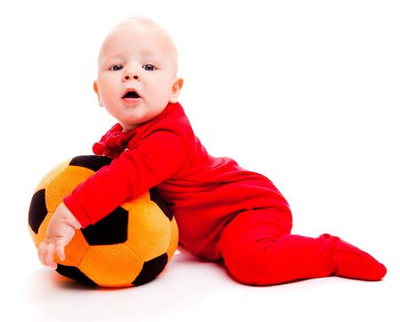 Surprised soccer baby in red holding ball in hands photo