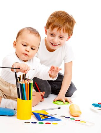Baby and preschool brothers drawing, isolated photo