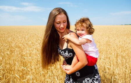 Mother holding her lovely daughter in wheat field photo