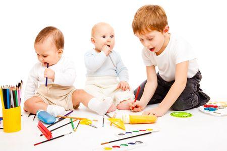 Three happy kids having art time, over white photo