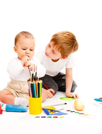 Little and preschool brothers drawing, isolated photo