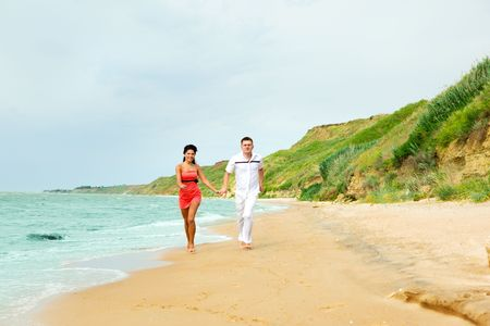 Lovely happy couple running along the beach photo
