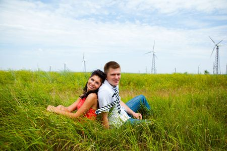 A young couple sitting in the meadow Stock Photo - 6838643