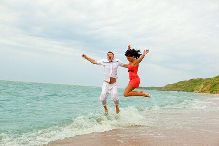Alegría en el agua - una feliz pareja saltando en las ondas