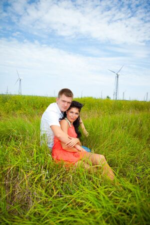 Romantic couple sit hugging at the meadow Stock Photo - 6838658
