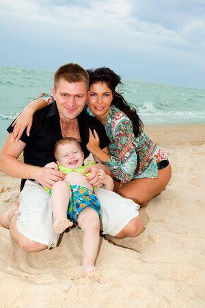 Happy family of three at the beach photo