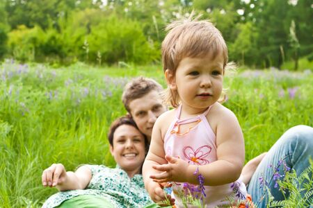A happy baby girl in the meadow, parents looking at her photo