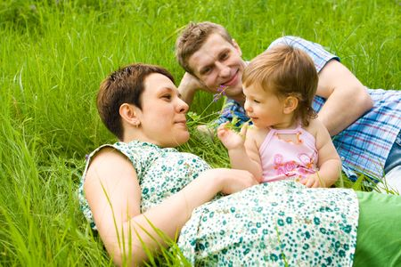 Young family having fun  in the spring grass photo