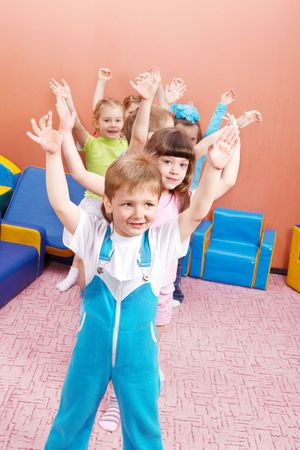 Group of joyful kids with their hands up Stock Photo - 6838742