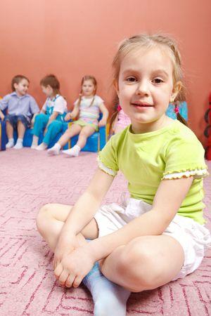 A cute preschool girl sitting, her friends in the background Stock Photo - 6838729