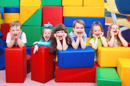 kid friendly: Group of joyful kids hiding behind large leather blocks Stock Photo