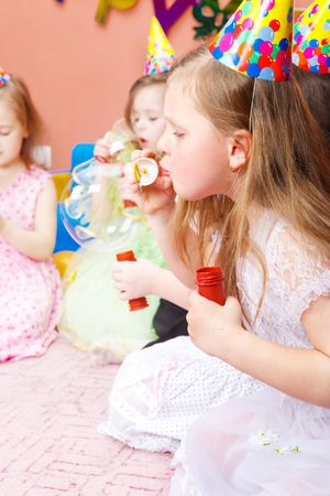 Kids blowing bubbles, a girl in front makes the big one Stock Photo - 6899102