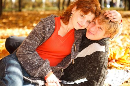 Young couple sitting on yellow leaves in park Stock Photo - 6899774