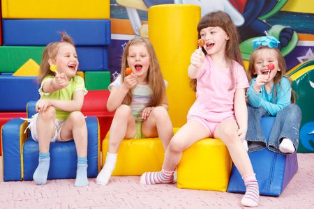little girl sitting: Happy preschool girls with lollipops in hands
