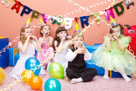 children party: Group of preschool kids with the party horns
