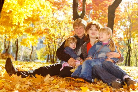 Young family in autumn park sitting  on yellow leaves