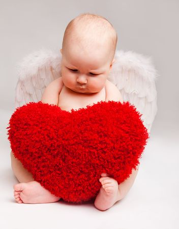 Cute happy valentine angel playing with red heart Stock Photo - 6899609