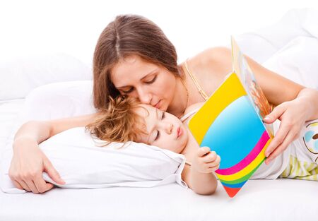 Mom kissing her toddler daughter who reads a kids book photo