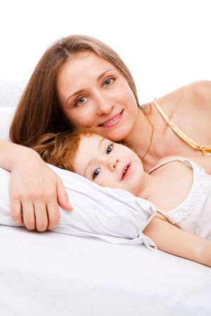 Beautiful mother and daughter lying on the pillow photo