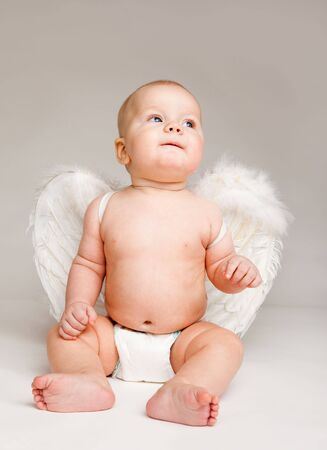 Baby angel in diaper with white wings, over grey photo