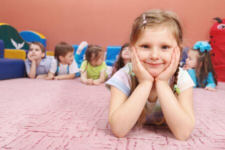 A cute preschool girl sitting, her friends in the background Stock Photo - 6899488