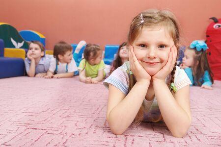 A cute preschool girl sitting, her friends in the background Stock Photo - 6899488