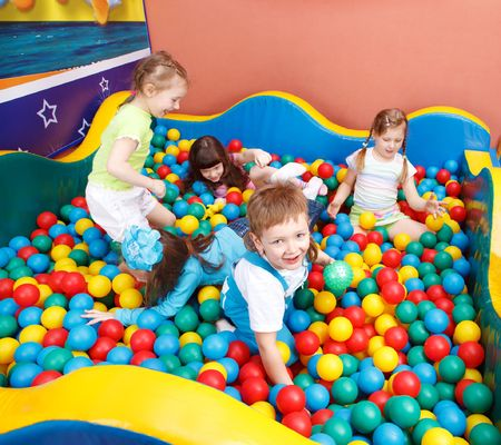 Happy kids playing in the colorful balls photo