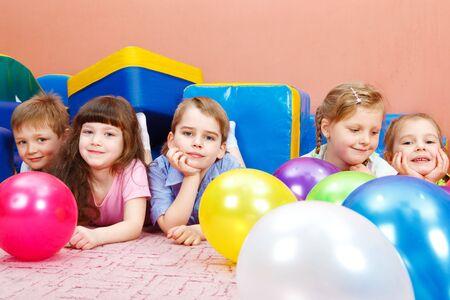 Sweet preschool children lying on floor among balloons photo
