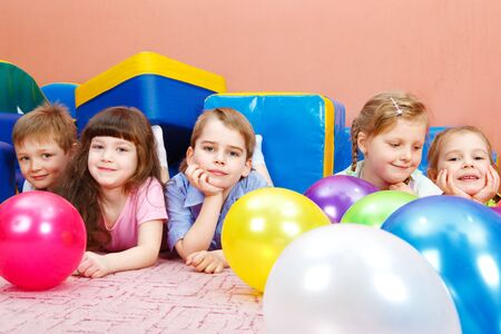 kindergarten toys: Sweet preschool children lying on floor among balloons Stock Photo