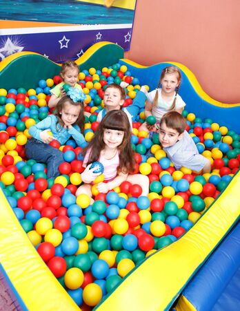 Joyful preschool kids playing in the colorful balls photo