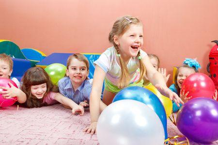 ni�os sentados: Un grupo de ni�os felices jugando con globos de colores Foto de archivo