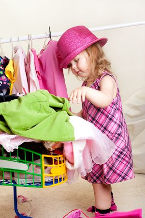 Toddler girl in pink hat putting clothes into trolley photo