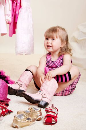 A cute fashionable girl trying on glamour boots photo